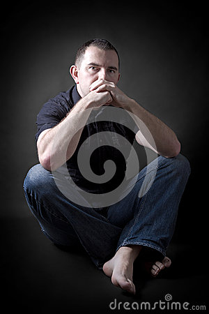 Low-key portrait of man sitting in dark