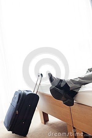 Low Section Of Businessman Lying On Bed Beside Luggage In
