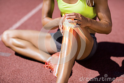 Low section of female athlete suffering from knee pain Stock Photo