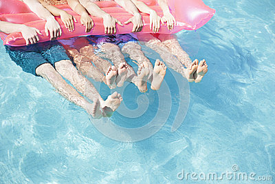 Low section of four friends in a pool holding onto an inflatable raft with feet sticking out of the water