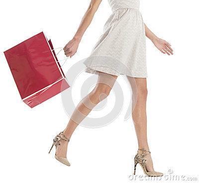 Low Section Of Woman Walking With Shopping Bag