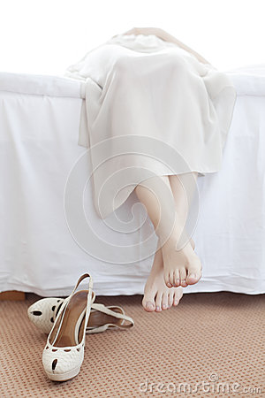 Low Section Of Young Woman Lying In Bed With Shoes On