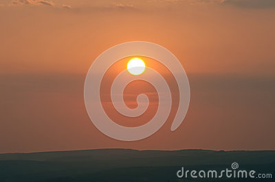 Low setting sun over distant landscape