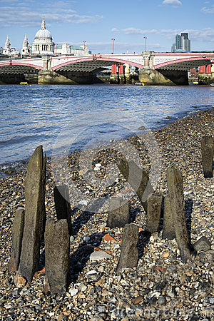 Low tide River Thames and London city skyline including St Paul