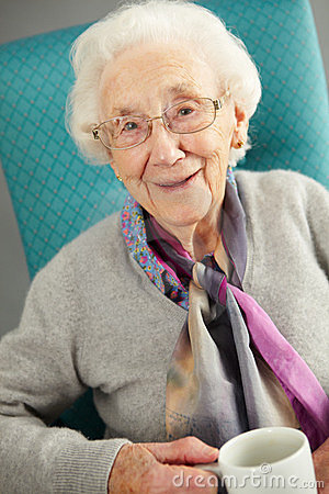 Ältere Frau, die bequemen trinkenden Tee schaut