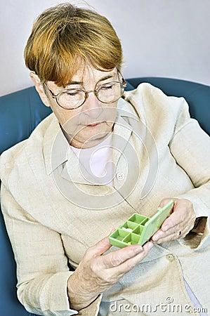 Ältere Frau mit Pillekasten