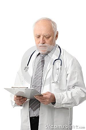 Älterer Doktor, der Papiere betrachtet