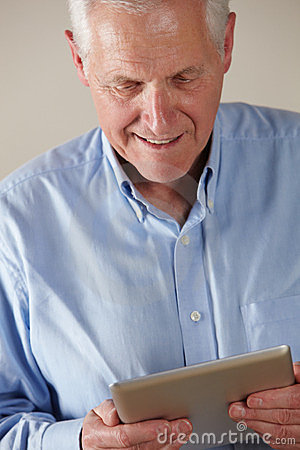 Älterer Mann, der Tablette verwendet