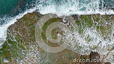 Lucht Mening De overzeese golven die met schuim en nevel aan steenachtige kust Mooie vrouw bespatten ligt op rotsachtig strand stock video