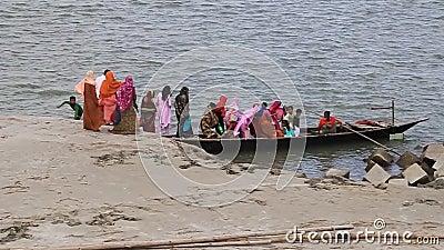 Ludzie wchodzą na pokład łodzi w brzegach rzeki Jamuna w Sariakandi Ghat niedaleko Bogry, Bangladesz zbiory