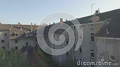 Luftschuß eines ghosttown, langsamer Aufstieg vorwärts vor einer schäbigen überwucherten Reihe von Häusern, beendend mit einem Pa stock video footage