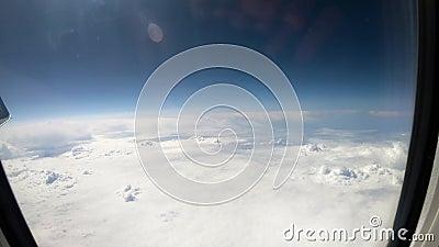 Luftsicht auf weiße Wolken und blauen Himmel aus dem Flugzeugfenster in der Kabine stock footage