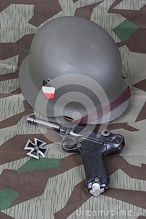Luger P08 Parabellum handgun, helm and medal Iron Cross on camouflaged background