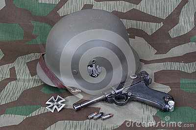 Parabellum handgun, helm and medal Iron Cross on camouflaged background