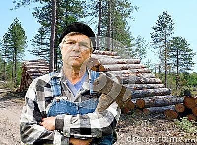 Lumberjack portrait against a stack of logs