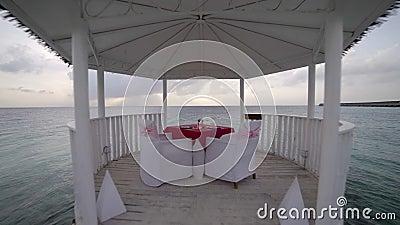 Luna de miel en centro turístico exótico, casa de planta baja con los vidrios y platos en la playa tropical de la tabla contra el metrajes