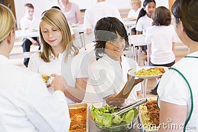 Lunchladies Umhüllungplatten des Mittagessens in einer Schule