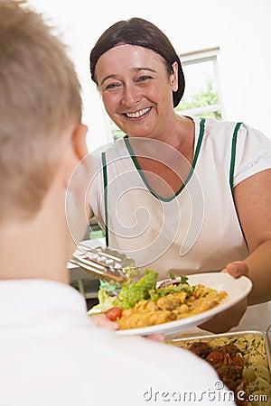 Lunchlady Umhüllungplatte des Mittagessens in einer Schule