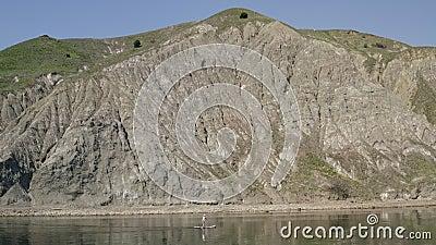 Lungo la riva contro fondo le montagne sup l'uomo di galleggiamento Attivit? dell'acqua video d archivio