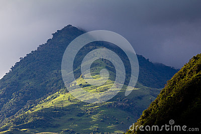 Lush green Andean landscape and rain clouds
