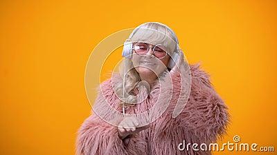Lustige kindische gealterte Dame in der netten Ausstattung vortäuschend, DJ, Hobby und Träume zu sein stock footage