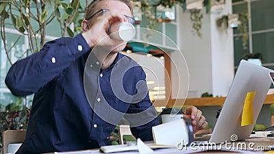 Lustiger verrückter Geschäftsmann mit Koffein-Sucht-trinkendem Kaffee und auf Laptop im Büro sehr schnell schreiben 4K stock video