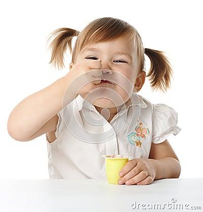 Lustiges kleines Mädchen isst Joghurt