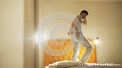 Lustiges Tanzen des jungen Mannes auf Bett am Abend bevor dem Schlafen stock footage