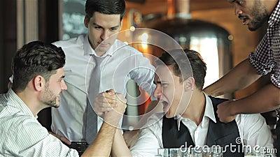 Lutte de quatre amis sur leur bière de boissons de mains banque de vidéos