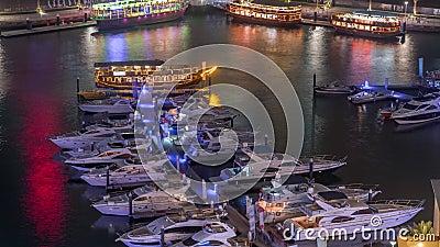 Luxejachten geparkeerd op de pier in Dubai Marina Bay met tijdslimiet voor nachtzicht vanuit de stad stock videobeelden