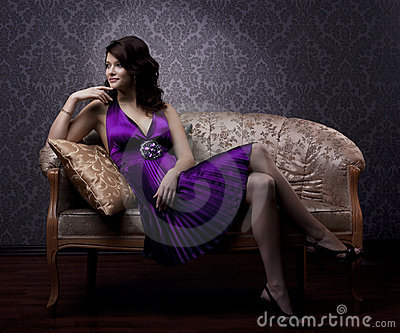 Luxurious woman sitting on a gold vintage couch