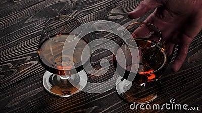 Luxury brandy Hand tar ett av två glas med gyllene konjak från träbord Brandy, konjak, sniftare, gångjärn Långsam rörelse 4K