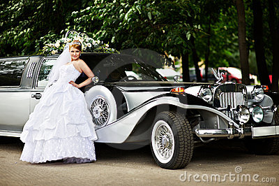 Luxury bride in wedding dress about limousine