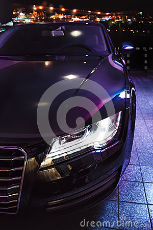 Luxury car at the parking in front of the night city
