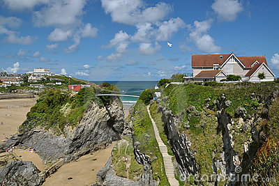 Luxury home on cliffs, tidal sea beach, blue sky