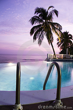 Luxury infinity swimming pool caribbean sunset