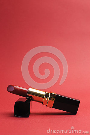 Luxury red lipstick against a red background, vertical with copy space