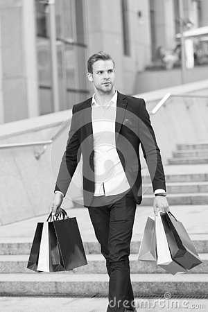 Free Luxury Shopping. Boutique Gallery Client. Man Shopper Carries Shopping Bags Urban Background. Successful Businessman Stock Photos - 133629943