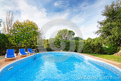 Luxury summer swimming pool with sun loungers.