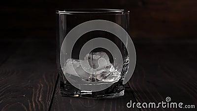 Luxury whiskey Iskuber faller i ett glas whisky på ett träbord mot träbakgrund Skotsk i tumlare