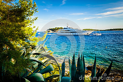 Luxury yacht anchored in a beautiful bay surrounded by greenery