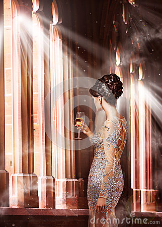 Luxury. Young Woman in Evening Dress with Glass of Champagne Standing at the Window in Sunshine