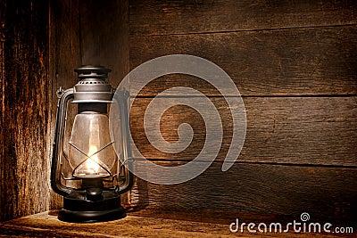 Luz velha da lanterna de querosene no celeiro rústico do país