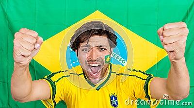 Lyckad idrottsman som ropar mot brasiliansk flagga