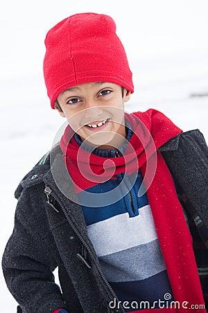 Lycklig östlig indisk pojke som leker i snowen