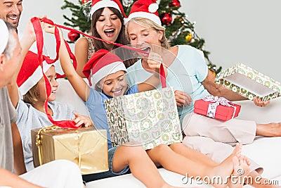 Lycklig familj på jul som tillsammans öppnar gåvor