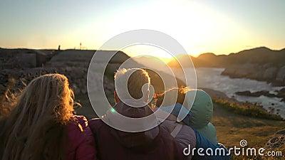 Lycklig familj som beundrar solnedgången eller soluppgången på den steniga norr kusten av havet lager videofilmer