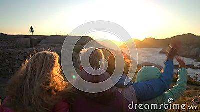 Lycklig familj som beundrar solnedgången eller soluppgången på den steniga norr kusten av havet stock video