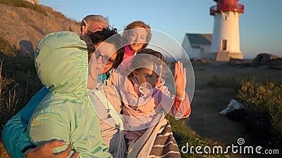 Lycklig familj som beundrar solnedgången eller soluppgången på den steniga norr kusten av havet med en gammal fyr arkivfilmer