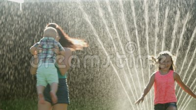 Lycklig familj som spelar i trädgården på gräsmattamodern med barn med vattenbestänkande stock video